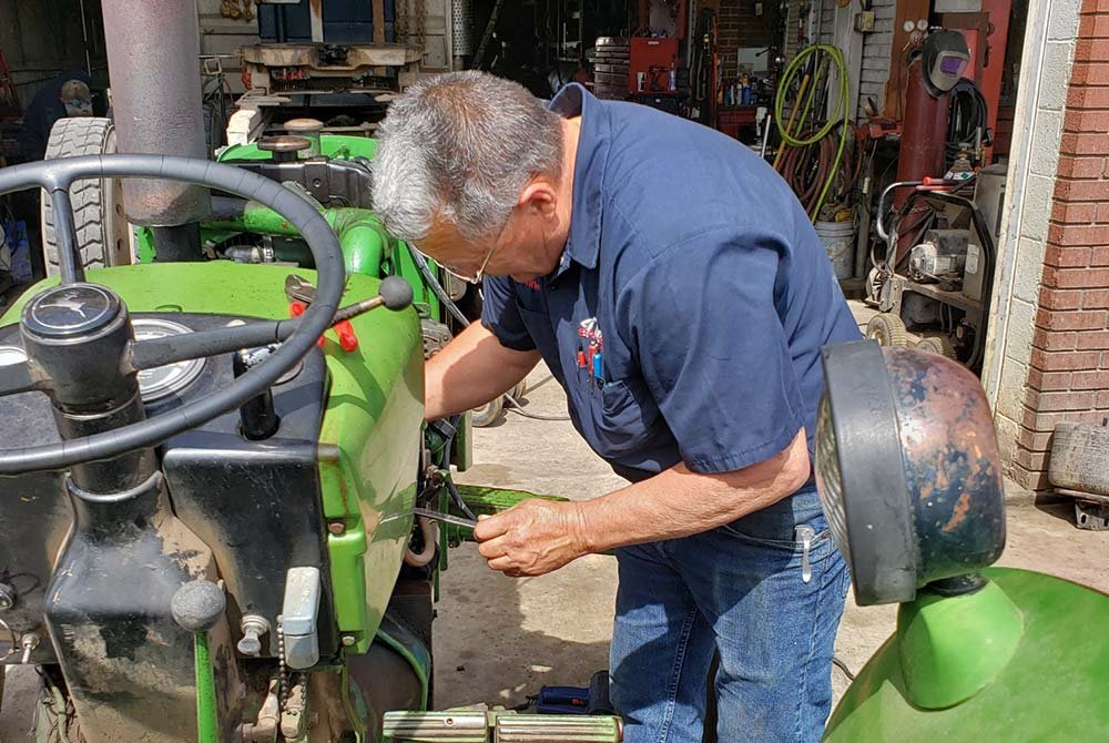 Man repairing tractor
