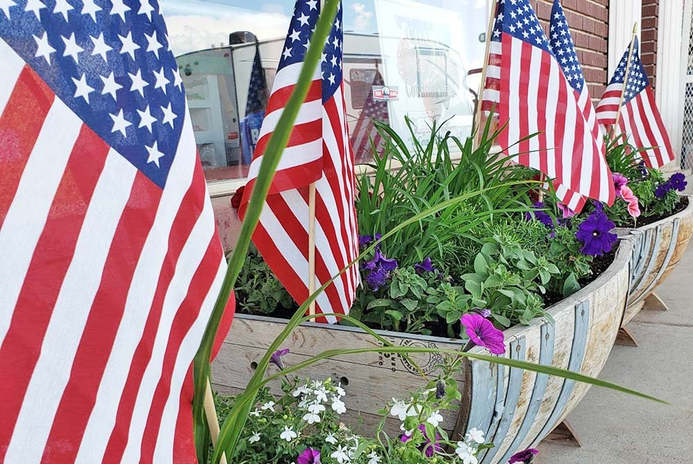 American flags in barrels with plants