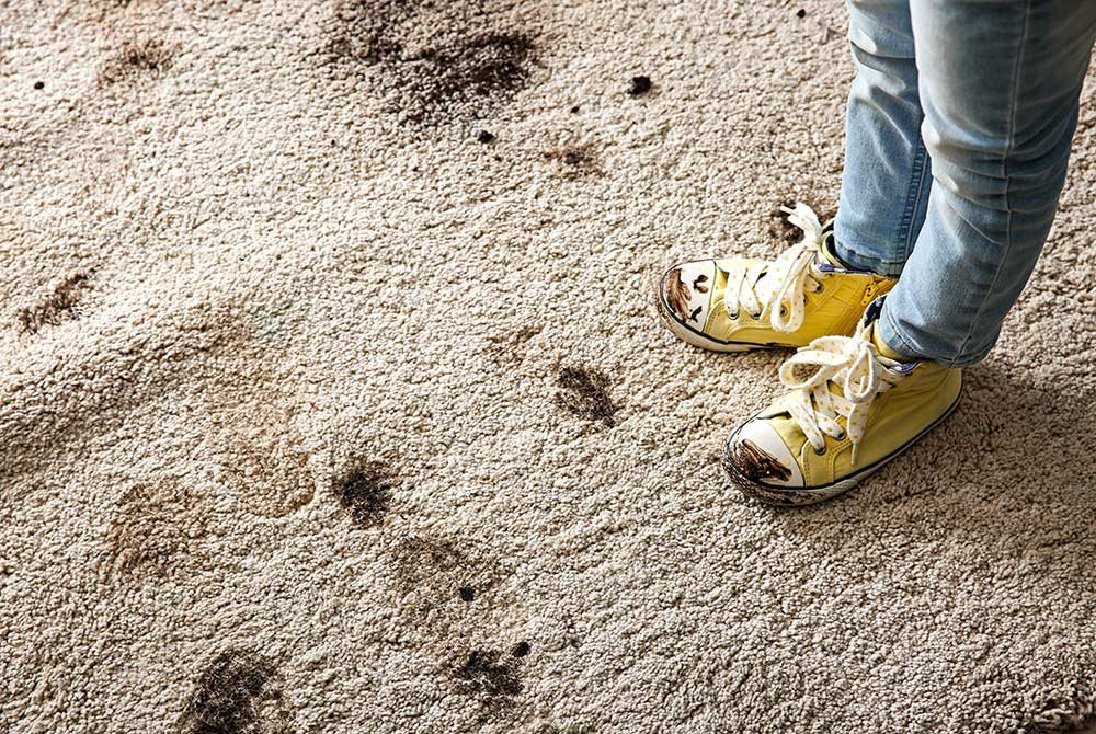 Person leaving muddy shoeprints on carpet