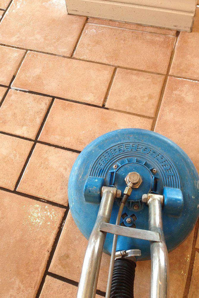 Machine scrubbing grout from stone flooring