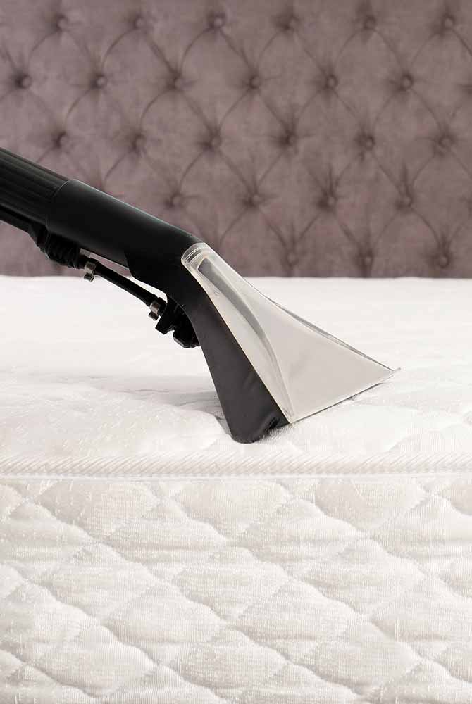 Vacuum cleaner vacuuming mattress on bed