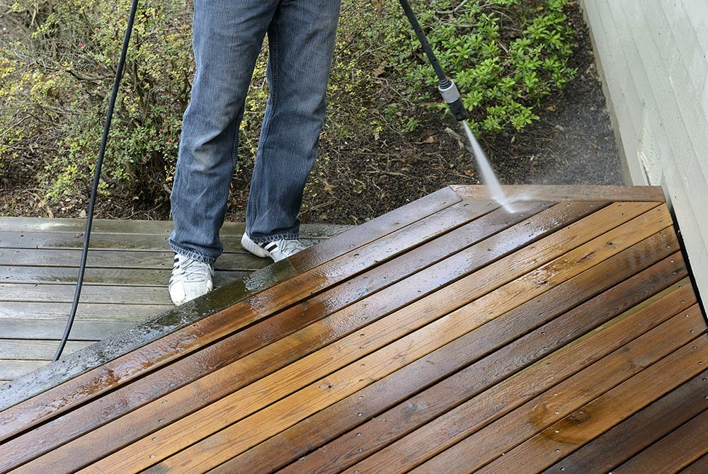 Person spraying wood patio with hose