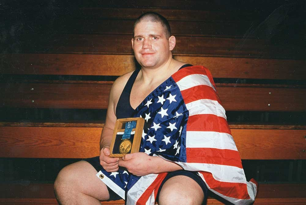 Rulon holding flag and gold medal on bench