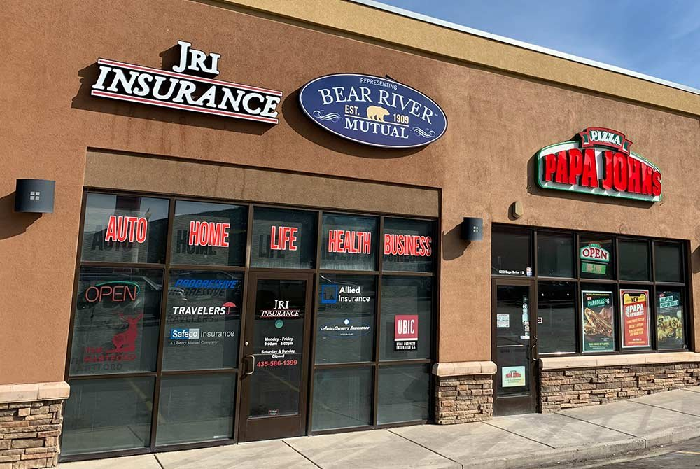 stucco building with signs that say JRI Insurance and Bear River Mutual