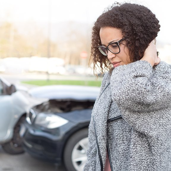 woman holding neck in front of auto accident