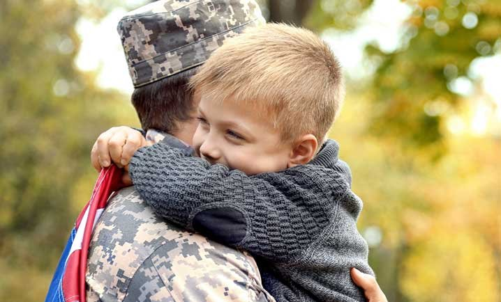 child holding father in military dress