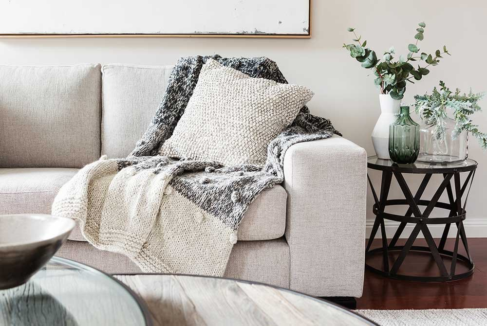 Pillow and blanket on couch by vases