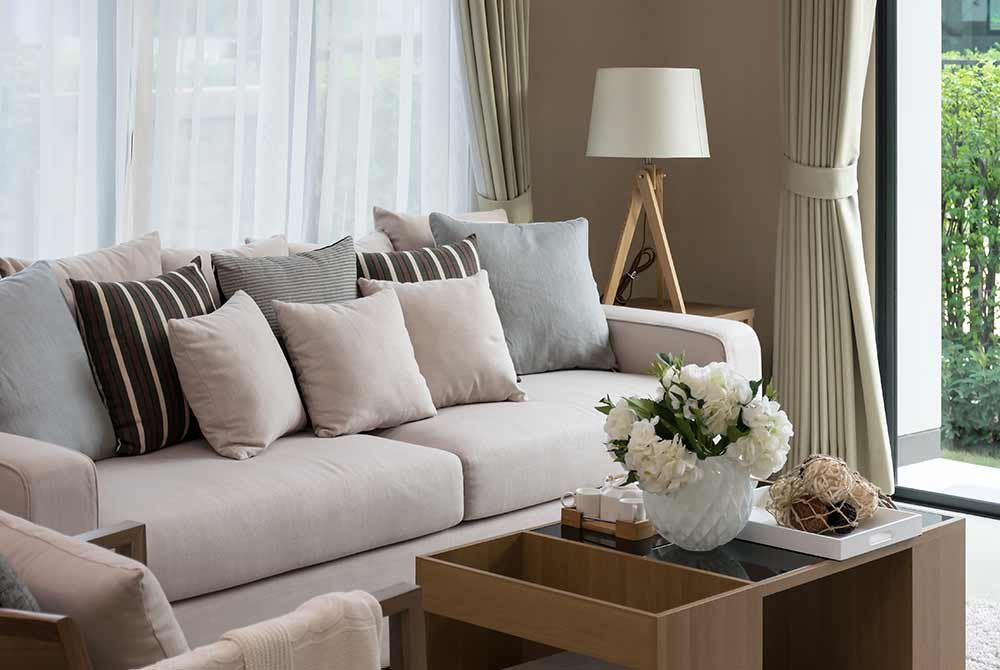 Pillows on couch next to coffee table with decorations