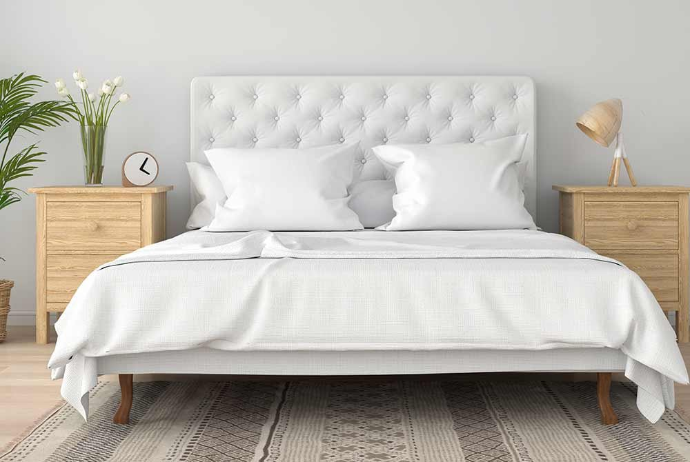 Bed with large headboard next to tabletops