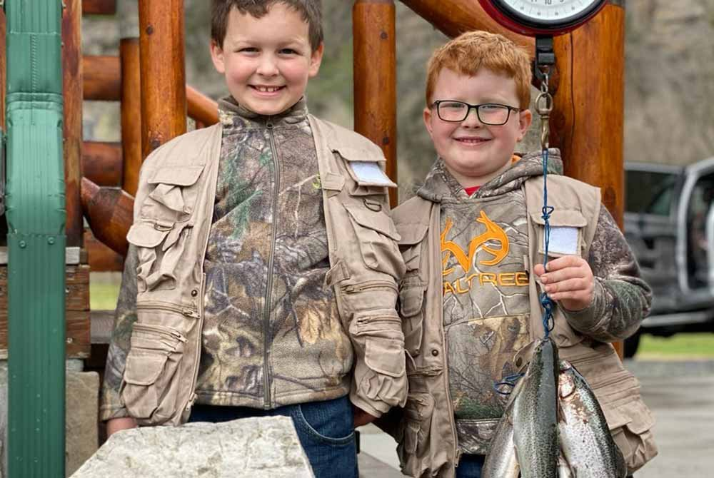 Two boys dressed in camo holding a bunch of fish