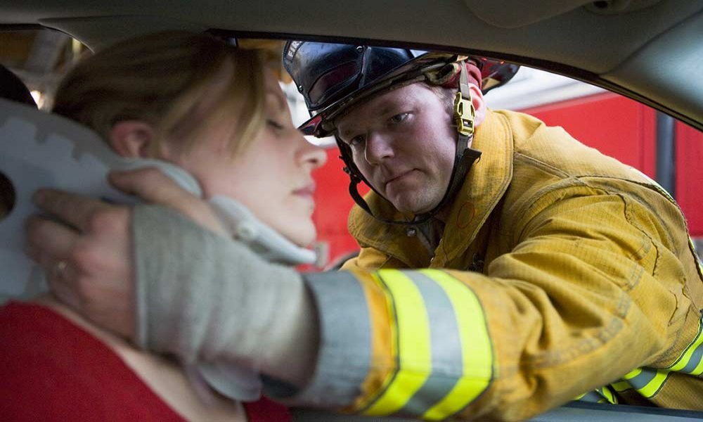 Fireman helping injured woman in car