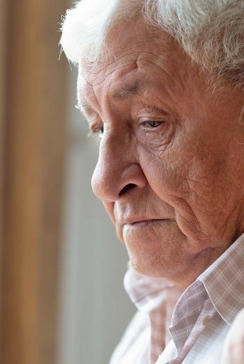Sad elderly gentleman standing near window