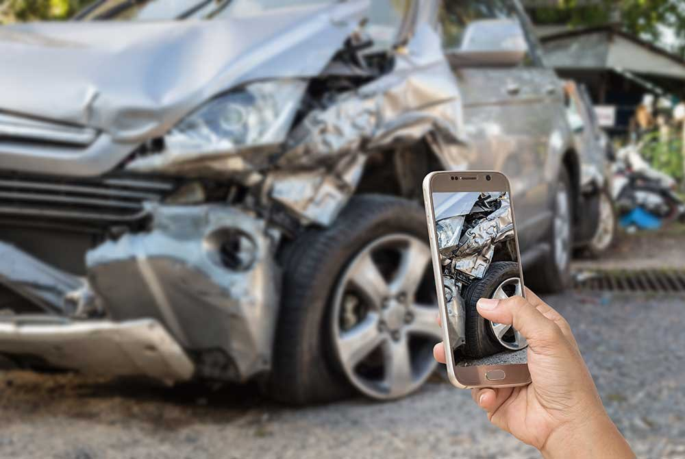 Person taking a photo of a car crash