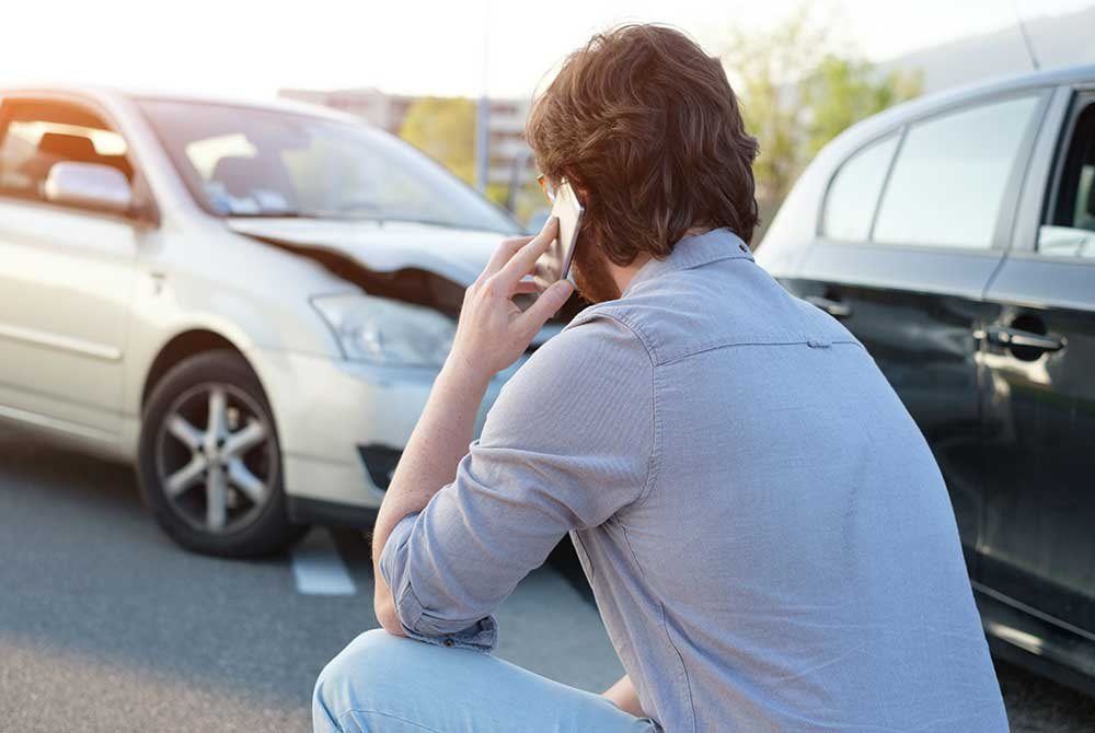 Man on phone next to car accident