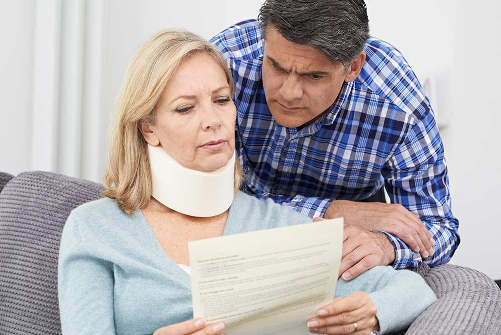 Woman with neck injury reading document with man