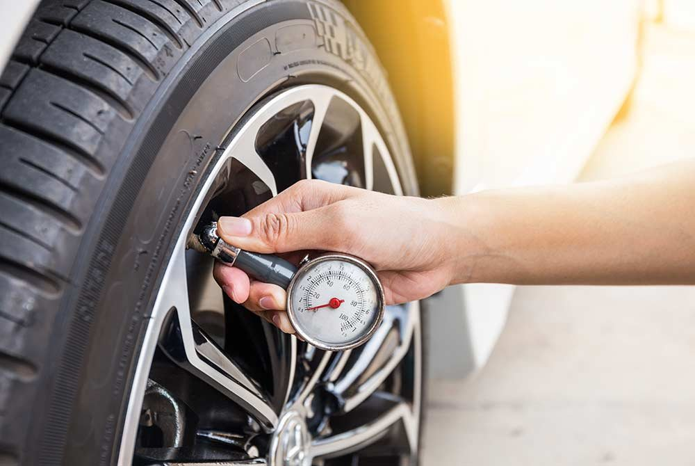 Person checking tire pressure with tool