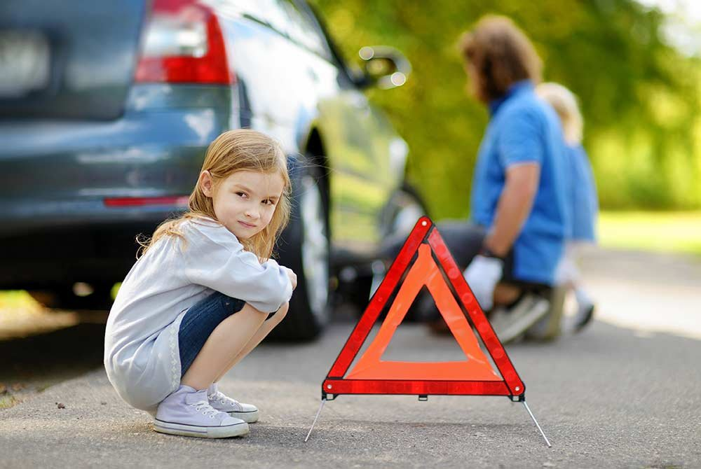 Girl sitting by car on side of road