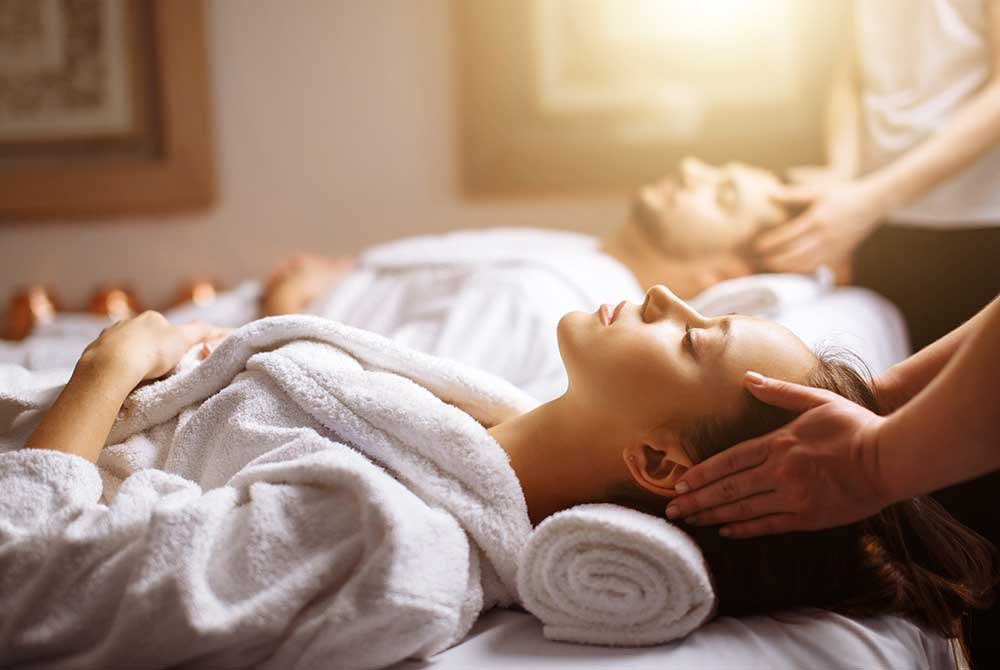 Man and women receiving massage in bathrobes