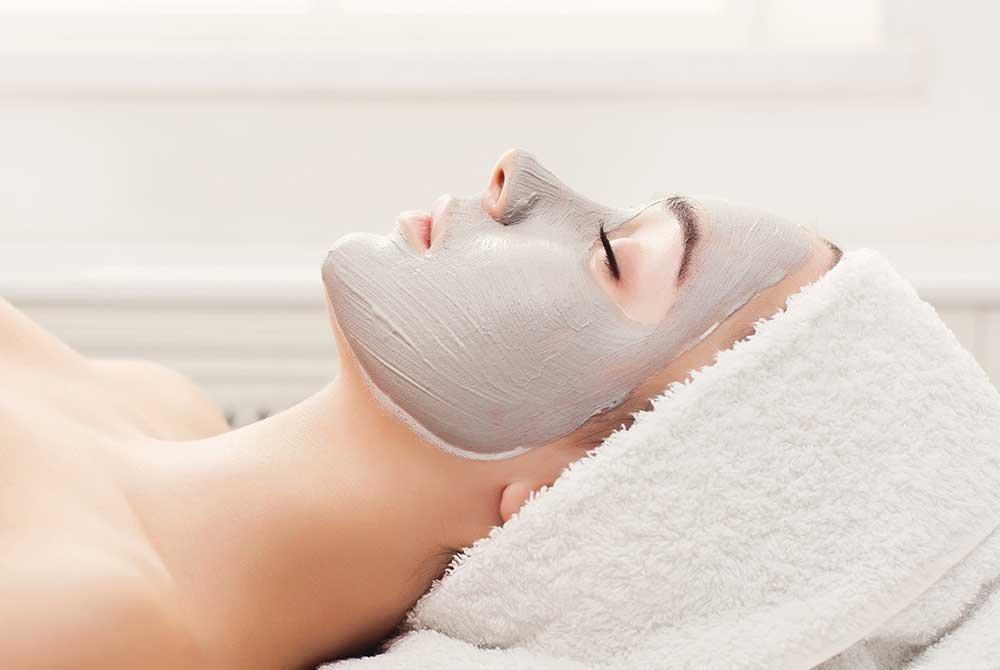 woman lying back wearing mud mask