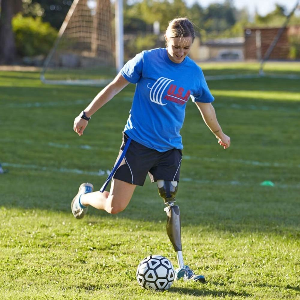 Woman with High Fidelity Interface leg prosthetic playing soccer