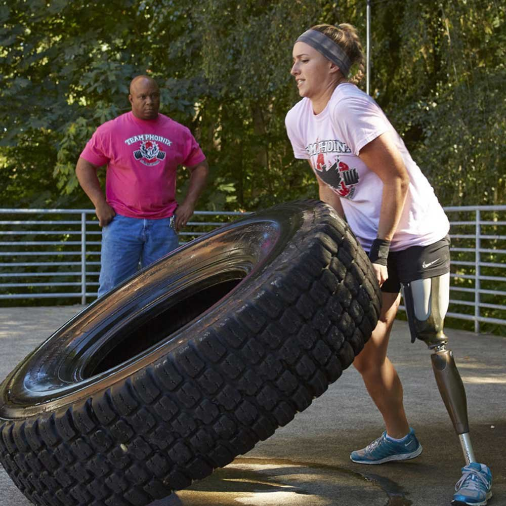 Woman with High Fidelity Interface leg prosthetic flipping a tire