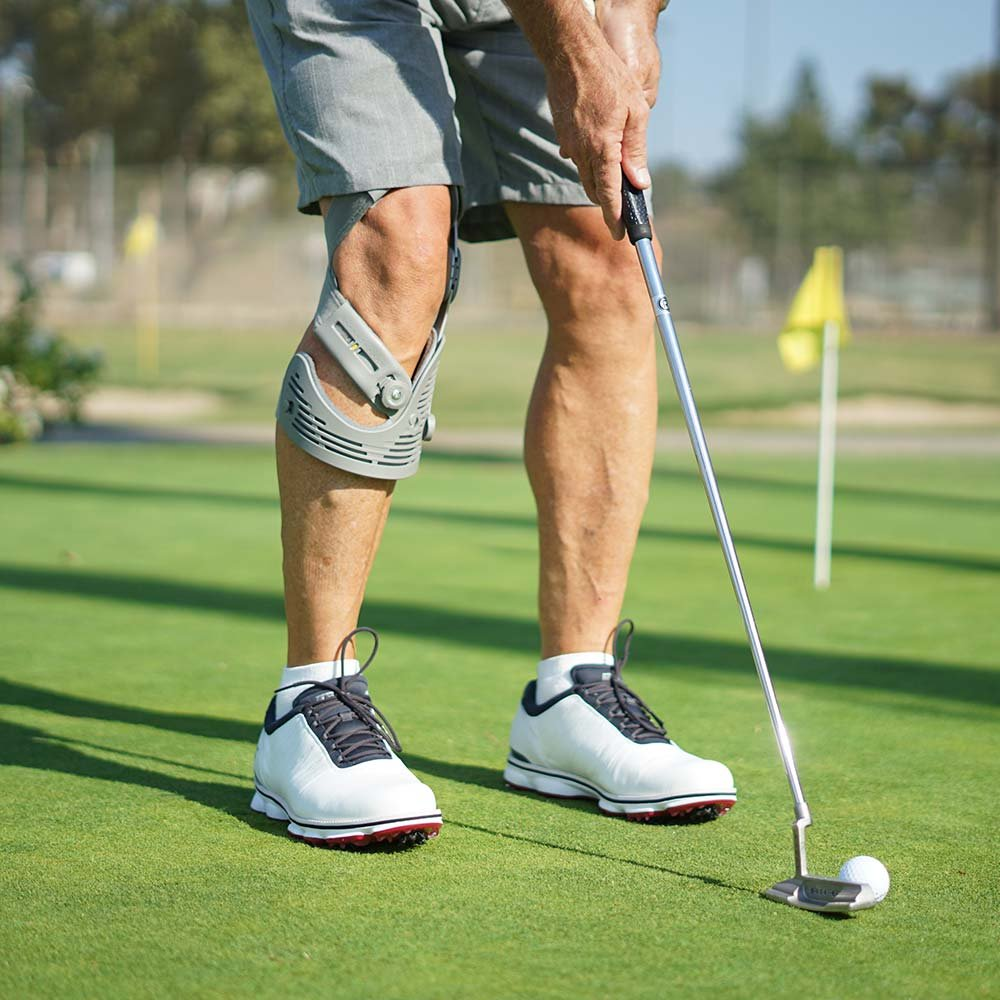 Man playing golf with a knee brace on