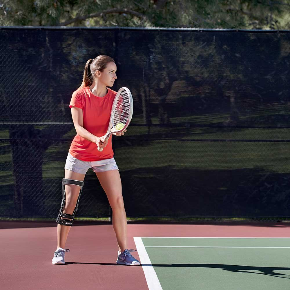 Woman playing tennis with a knee brace