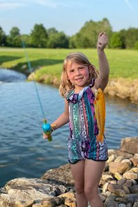 young girl in bathing suit with fishing pole