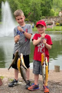 two young boys holding a group of fish