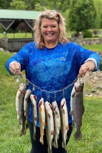 smiling woman holding eight fish on a string
