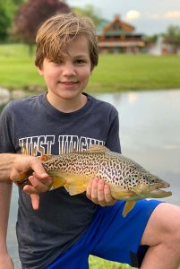 young man holding a medium fish