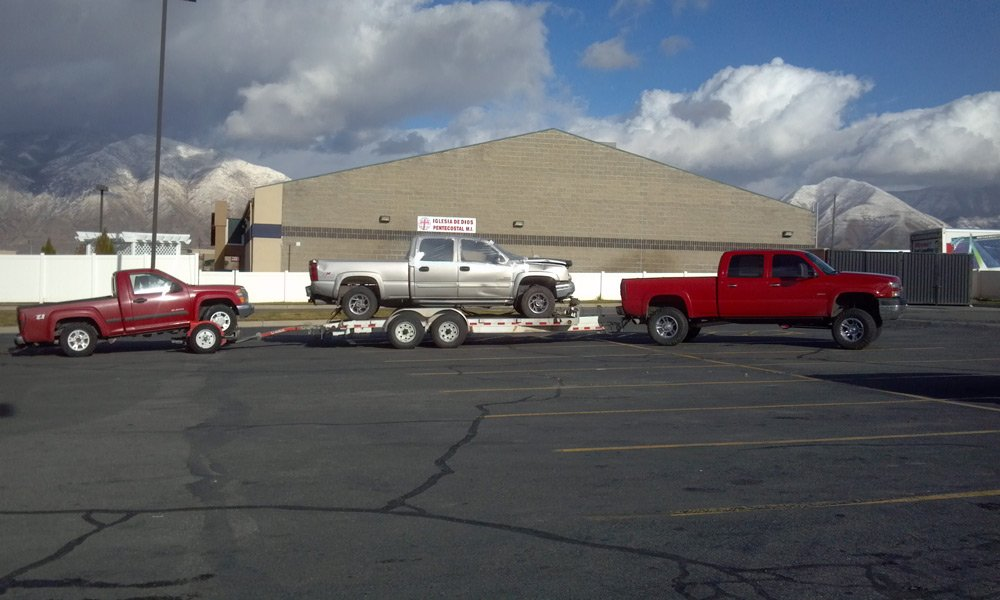 A Truck pulling two trucks on trailers