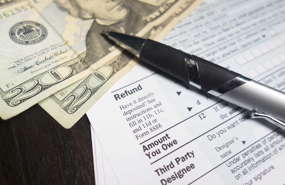 cash near pen and tax documents