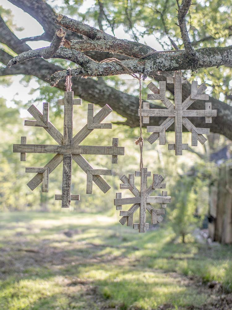 Repurposed wooden snowflakes hung in a tree
