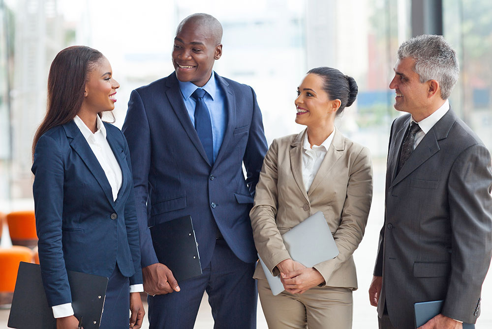 four people of diverse ethnicities in business attire