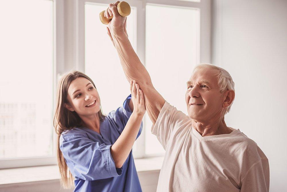 nurse helping senior patient lift weights