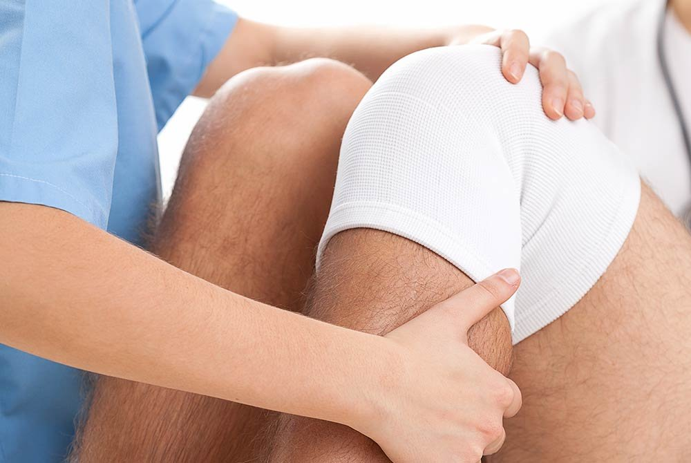 man receiving therapeutic treatment for his knee