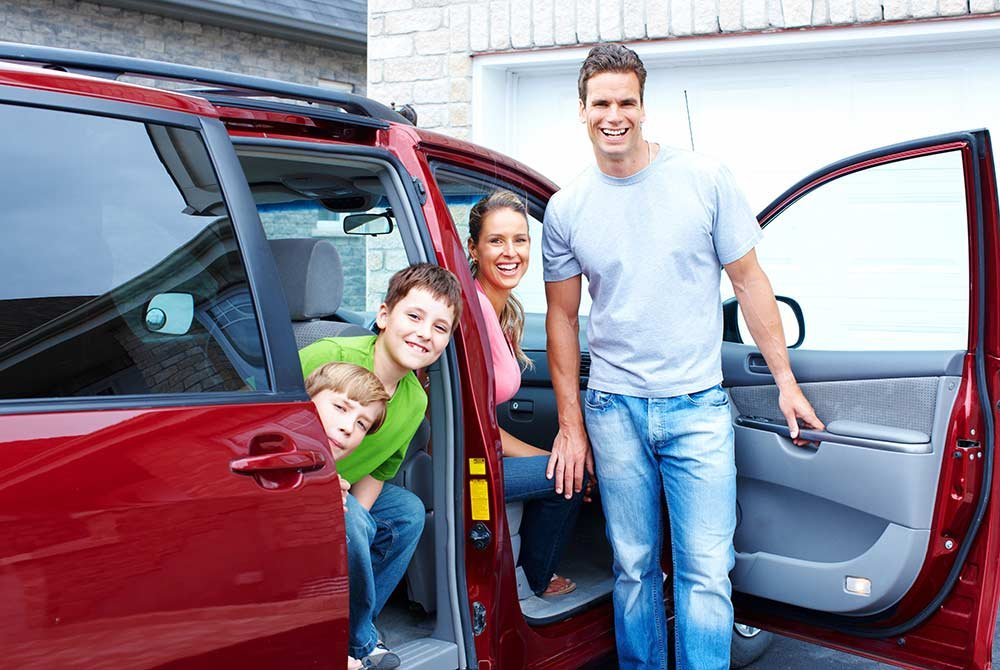 family standing or sitting in a vehicle
